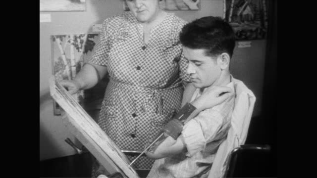vídeos de stock, filmes e b-roll de / mother of paralyzed artist gilbert provencher places a paintbrush in the painter's arm brace / cu of detailed painting / cu of several paintings... - brace