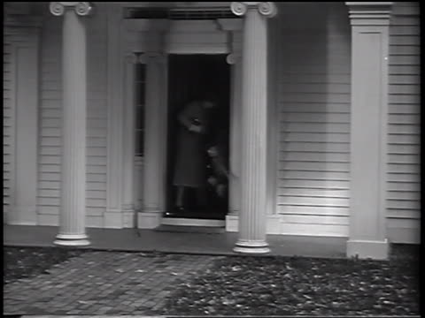 B/W 1937 mother opening door of house + two children run out / she follows them smiling / commercial
