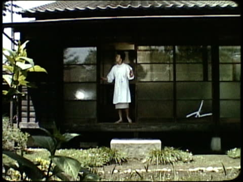 1963 MONTAGE Mother opening shutters of house and waking her sons sleeping on floor / Japan