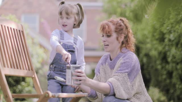 vídeos de stock e filmes b-roll de mother painting chair with daughter in garden - terreno