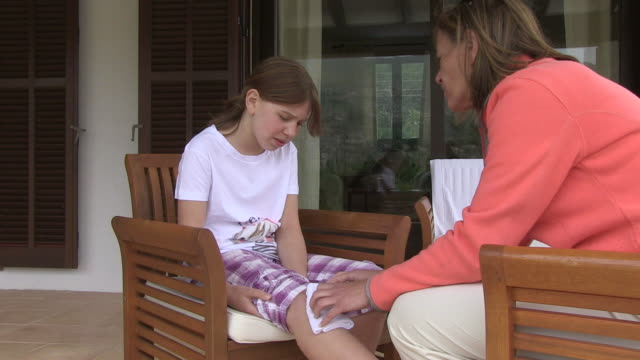 ms mother patches up wounding knee of her daughter / pollenca, mallorca, spain - wounded stock videos & royalty-free footage