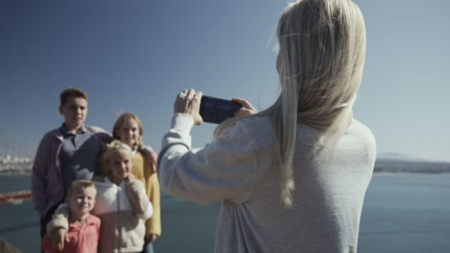 vídeos de stock e filmes b-roll de mother photographing children posing near golden gate bridge / san francisco, california, united states - família com quatro filhos