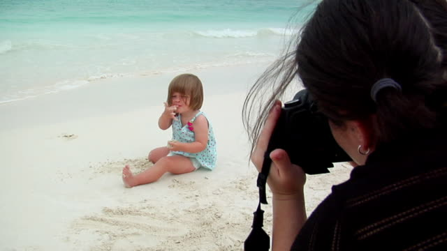 ws mother photographing daughter (18-23 months) playing in sand on beach, isla mujeres, quintana roo, mexico - 18 23 months bildbanksvideor och videomaterial från bakom kulisserna