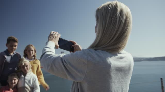 vidéos et rushes de mother photographing silly children posing near golden gate bridge / san francisco, california, united states - famille avec quatre enfants