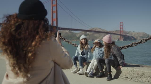 vídeos de stock e filmes b-roll de mother photographing silly children posing near golden gate bridge / san francisco, california, united states - língua humana