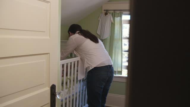 vídeos de stock e filmes b-roll de ms pan mother picking baby daughter (3-5 months) up from crib / seattle, washington state, usa - quarto do bebé