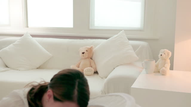 mother picking up baby and sitting on sofa - tutina video stock e b–roll