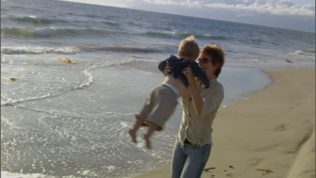 vidéos et rushes de slo mo ms zi cu mother picking up young son and spinning him around on beach / vista del mar, california, usa - mar