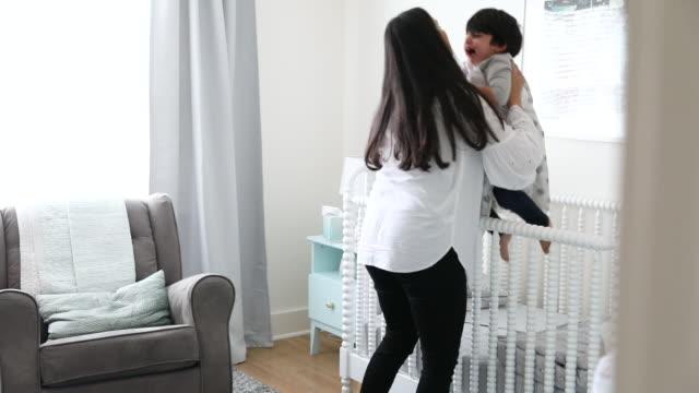 vídeos de stock e filmes b-roll de mother picks toddler son up out of crib after he wakes from his nap - quarto do bebé