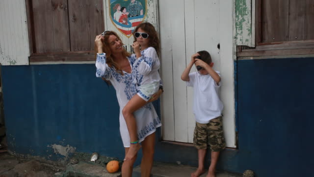 Mother picks up daughter while putting on matching sunglasses in matching outfits with daughter pointing and son standing with glasses on totally wrong.