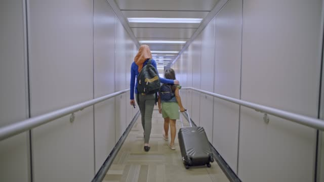 slo mo. mother places arm around young daughter's shoulders as they walk down airport jet bridge. - islam stock videos & royalty-free footage
