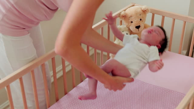 vidéos et rushes de mother placing baby in crib - positionner