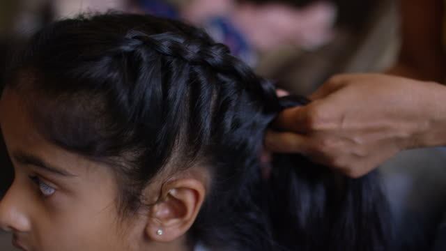 mother plaiting her daughter's hair - braided hair stock-videos und b-roll-filmmaterial