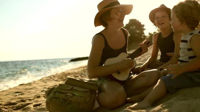 vídeos y material grabado en eventos de stock de madre tocando una guitarra con sus hijos en la playa - guitarrista
