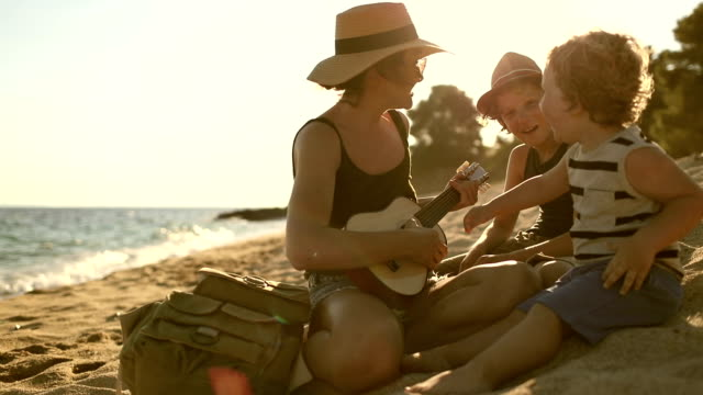 mother playing a guitar with her boys at the beach - country and western stock videos & royalty-free footage