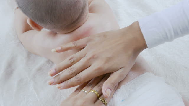 mother playing and massage baby - massage stock videos & royalty-free footage
