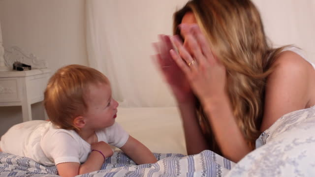cu mother playing peek-a-boo with baby girl (18-23 months) on bed / saint tropez, var, france - 18 23 months stock-videos und b-roll-filmmaterial