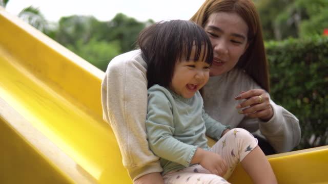 mamma spelar slider med dotter på playground - förälder och barn bildbanksvideor och videomaterial från bakom kulisserna