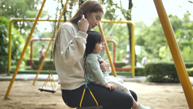 mother playing swing with child - swing stock videos & royalty-free footage