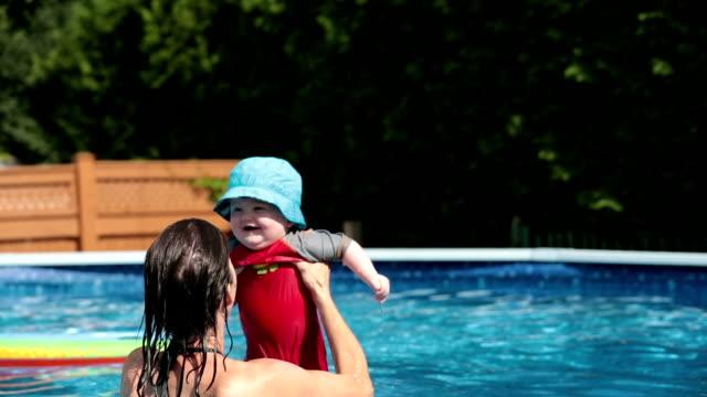 vidéos et rushes de mère, jouant avec le petit garçon dans la piscine - 2 5 mois