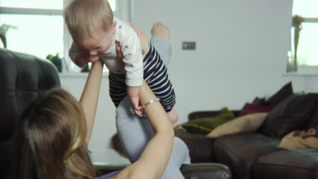 slo mo ms mother playing with baby boy (6-11 months) / london, united kingdom - picking up stock videos & royalty-free footage