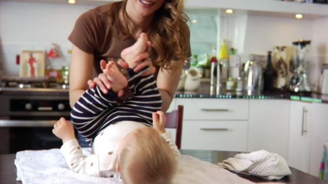 slo mo ms mother playing with baby boy (6-11 months) lying on kitchen table / london, united kingdom - 6 11 months stock videos & royalty-free footage