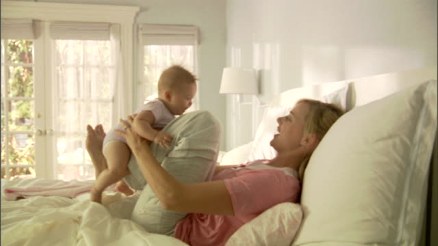 ms, mother playing with baby girl (6-9 months) on bed - 6 11 månader bildbanksvideor och videomaterial från bakom kulisserna