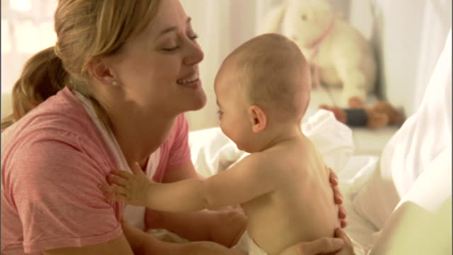 cu, mother playing with baby girl (6-9 months) on bed - 6 11 monate stock-videos und b-roll-filmmaterial