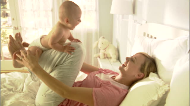 ms, mother playing with baby girl (6-9 months) on bed - nappy stock videos & royalty-free footage