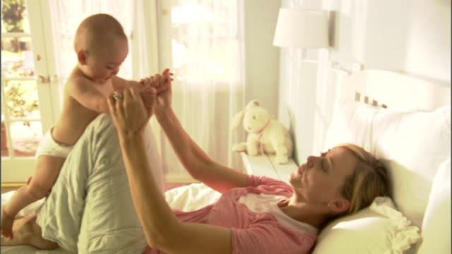 ms, mother playing with baby girl (6-9 months) on bed - picking up stock videos & royalty-free footage
