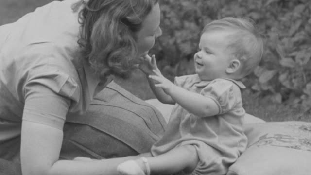 vídeos de stock, filmes e b-roll de 1947 ms mother playing with baby / united kingdom - etnia