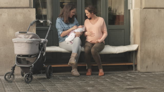 mother playing with baby while talking with friend - three wheeled pushchair stock videos & royalty-free footage