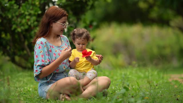 vídeos de stock e filmes b-roll de mother playing with daughter sitting on grass - sentar se
