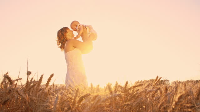 slo mo mother playing with her baby among wheat plants - sundress stock videos & royalty-free footage