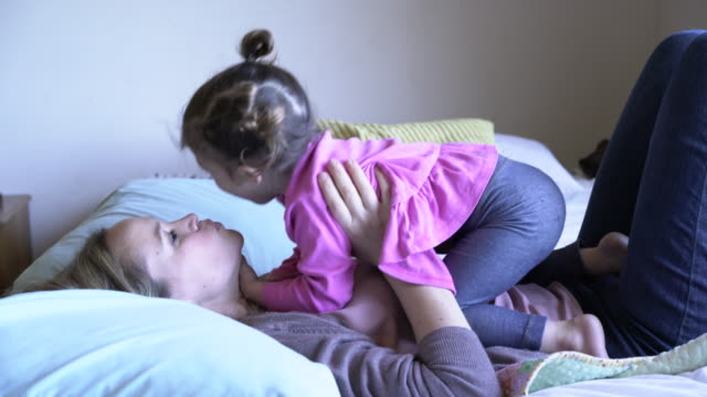 MS Mother playing with her daughter in bed.