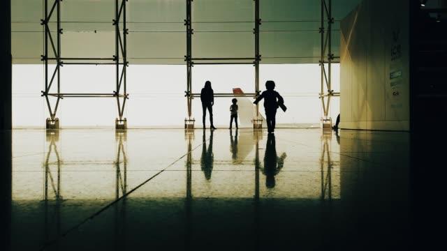 vídeos de stock, filmes e b-roll de matriz que joga com seus miúdos e o aeroporto - embarcar