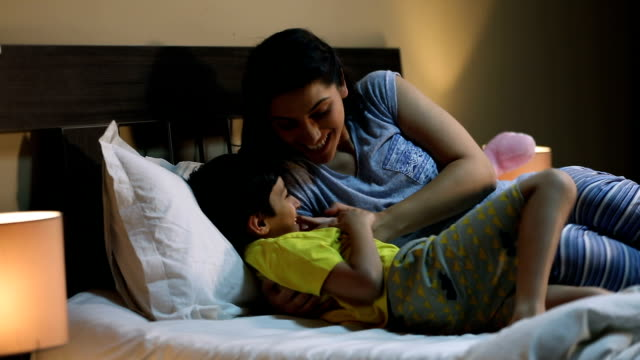 Mother playing with her son at home, Delhi, India