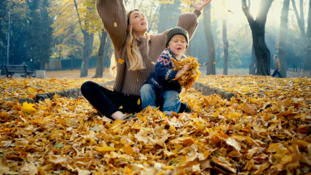 mother playing with little son in park in autumn - jumper stock videos & royalty-free footage