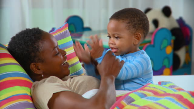CU, Mother playing with son (12-17 months) in bed, Richmond, Virginia, USA