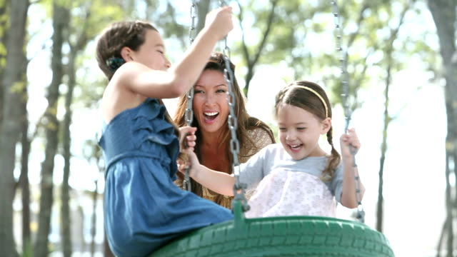 Mother playing with two girls at park, on tire swing