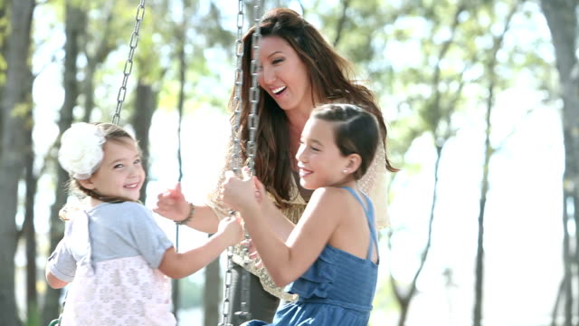 stockvideo's en b-roll-footage met moeder speelt met twee meiden in het park, op band-swing - 35 39 years