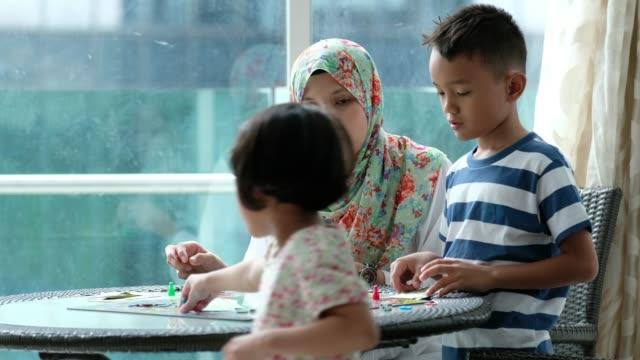 stockvideo's en b-roll-footage met moeder speelt een spel met haar kinderen - spelletjesavond