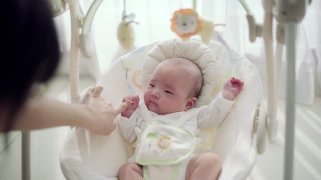 mother plays with baby girl in rocking chair - korean ethnicity stock videos & royalty-free footage