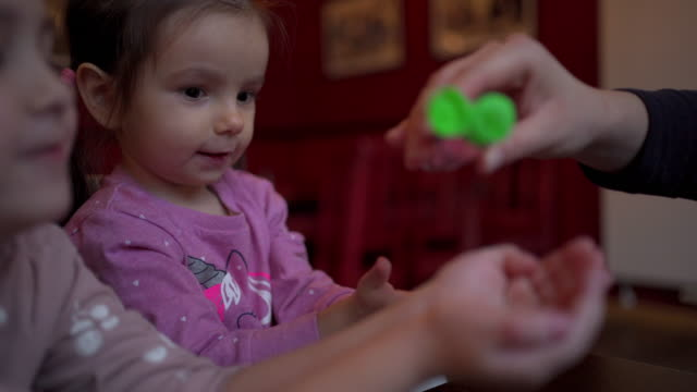mother pouring hand sanitizer into daughter's hand - innocenza video stock e b–roll