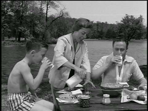vídeos de stock e filmes b-roll de b/w 1954 mother pouring milk for man + son at picnic table by lake / industrial - piquenique