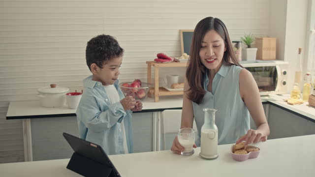 mother pouring milk into glasses for her boy having breakfast at home - table stock videos & royalty-free footage