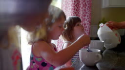A mother pours milk into her daughters' cereal bowls