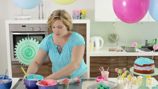 vidéos et rushes de mother prepares children's birthday party in the kitchen - decorating cup cakes - femmes d'âge moyen