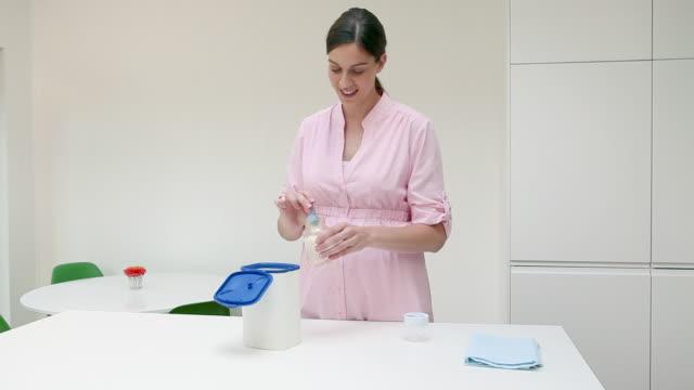vídeos y material grabado en eventos de stock de mother preparing baby formula - preparación