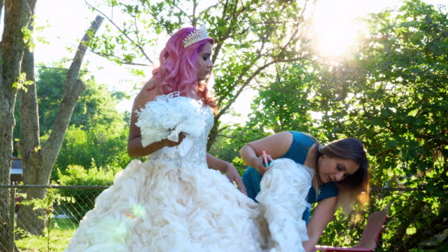 ms pan mother preparing daughters quinceanera gown in backyard - 14 15 anni video stock e b–roll